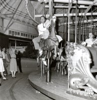 man and woman riding a carousel at an outing of Bristol Brass Company employees celebrating the company's 100th anniversary