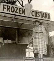 young child admires a rolling-pin, in front of a frozen custard stand, with a woman at an outing of Bristol Brass Company employees celebrating the company's 100th anniversary