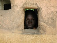 boy in the Central African Republic peeks out of a window of a school