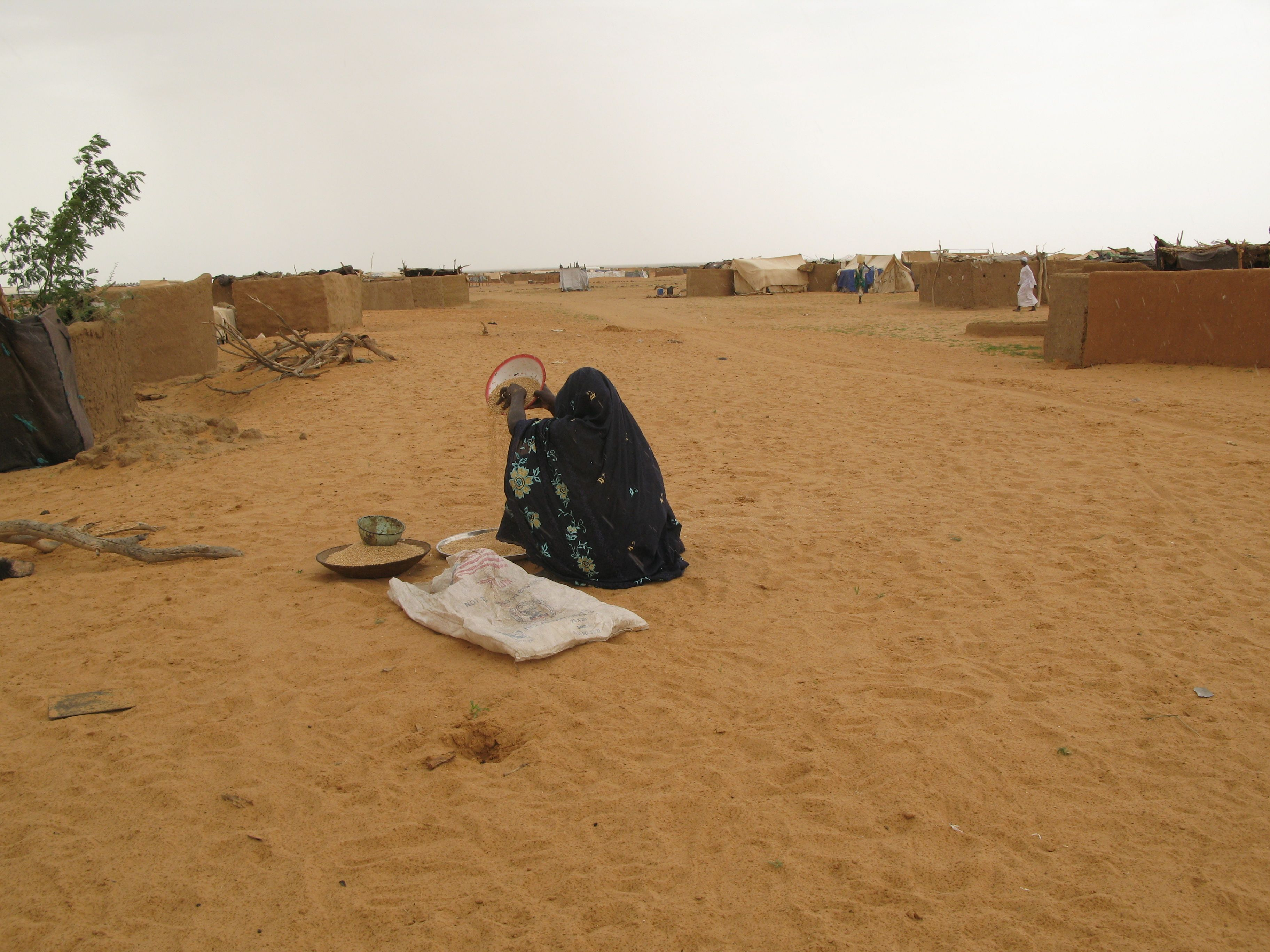 Darfuri woman pours grain at the Oure Cassoni refugee camp in Chad, near the border with Darfur