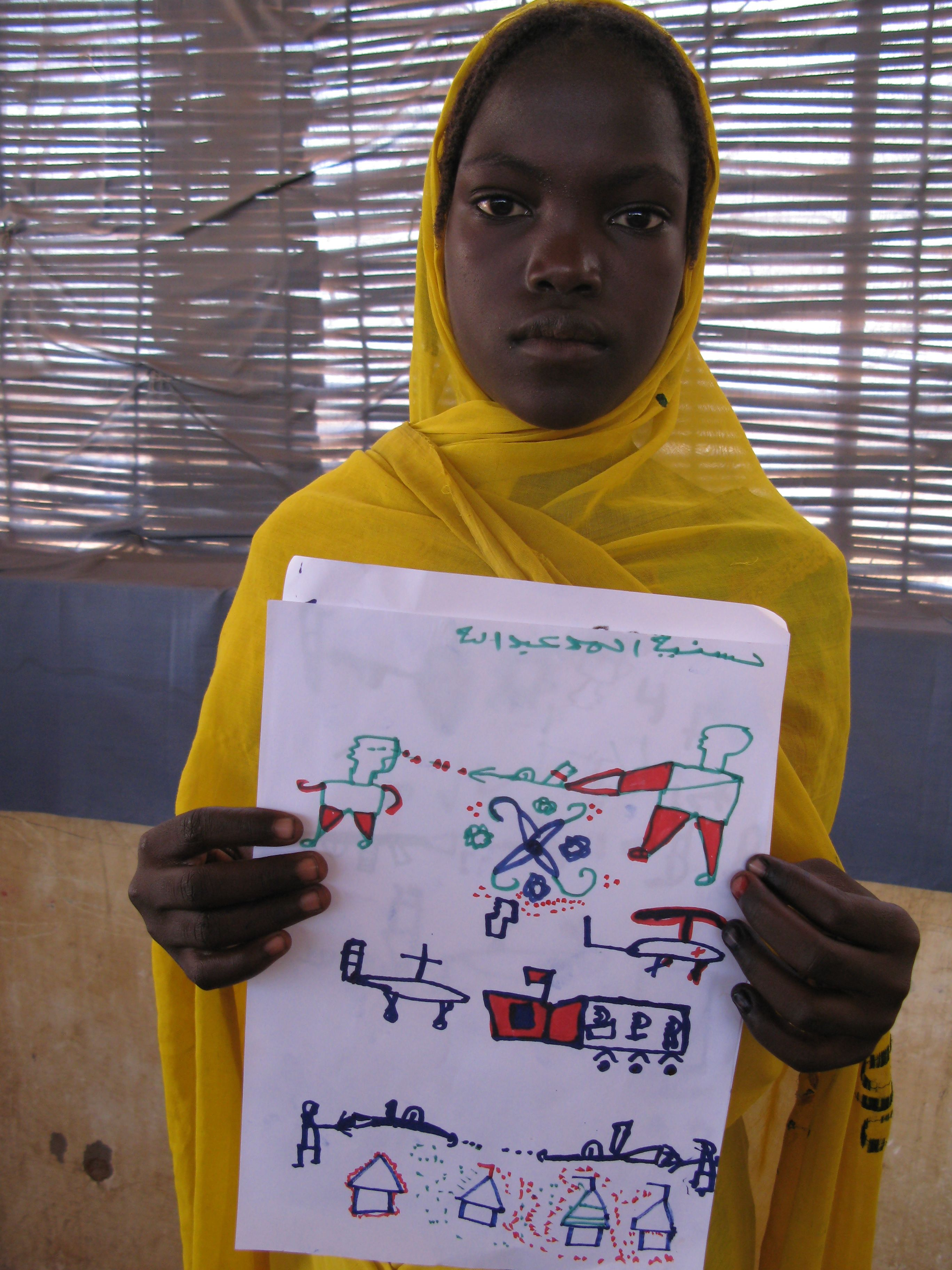 Girl in the Djabal Refugee Camp holds a drawing of the violence she witnessed