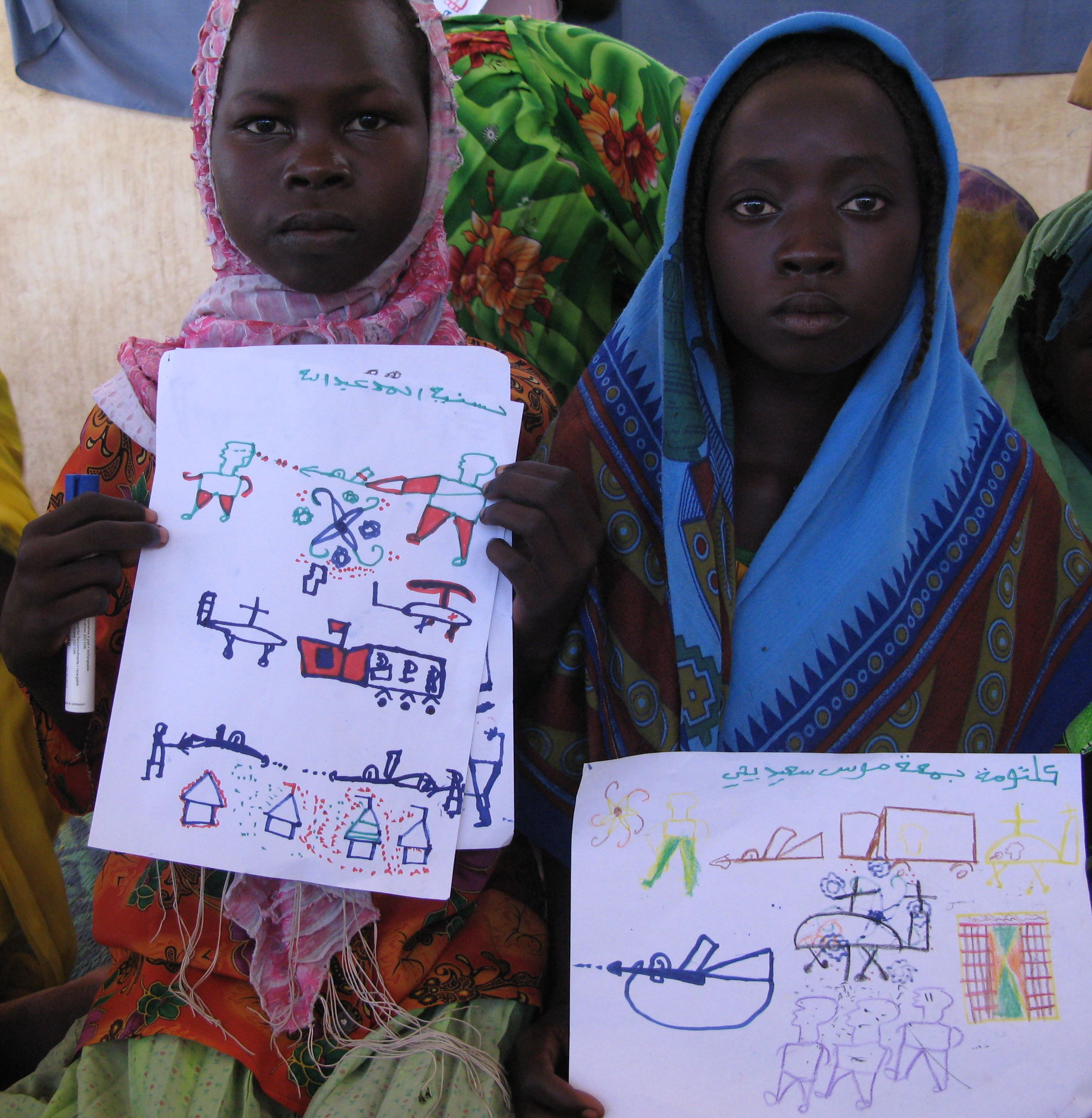 Darfuri girls in the Djabal Refugee Camp hold drawings of the violence they witnessed
