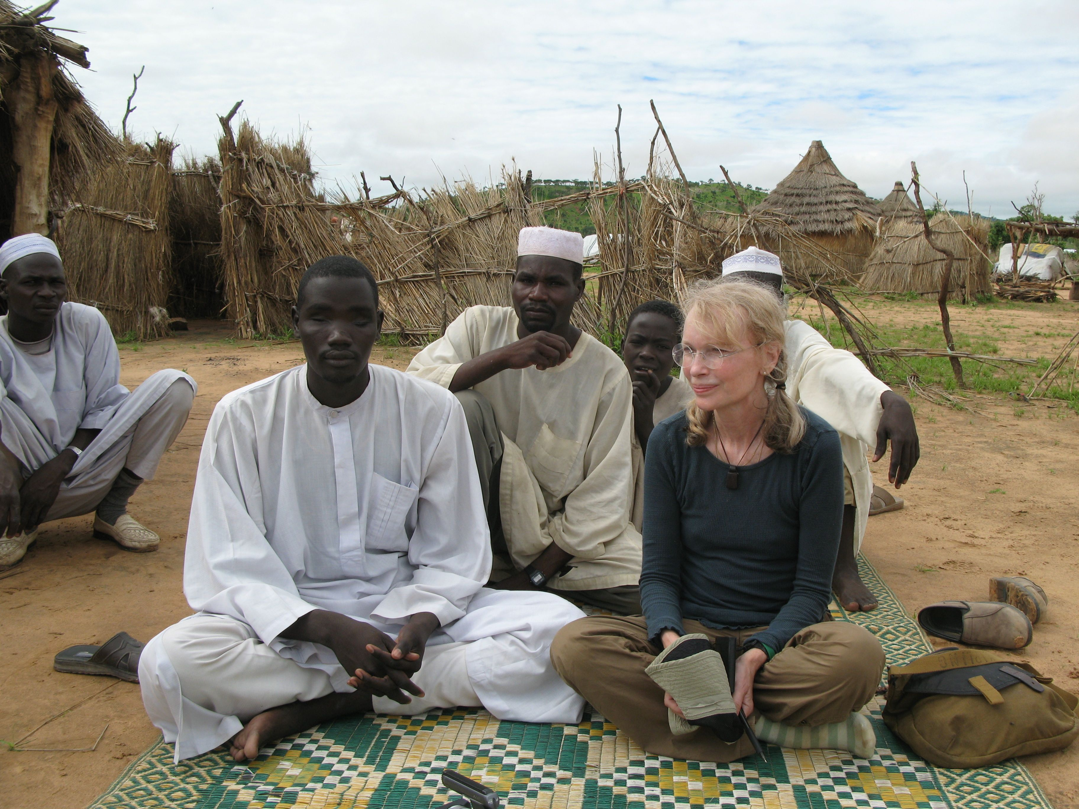 Actor and humanitarian Mia Farrow sits with Darfuri men at the Gouroukoum camp.