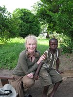 Actor and humanitarian Mia Farrow sits with a young Darfuri survivor of violence
