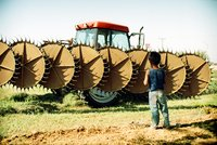Young Migrant Boy Stands Before Lethal Farm Equipment
